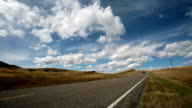 Low angle 3/4 view of highway on prairie with single car driving by under puffy clouded blue sky.