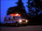 low angle PAN ambulance with flashing lights drives past camera at dusk