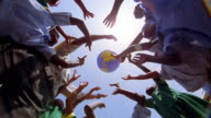 low angle MS Black schoolchildren + teacher playing with inflatable globe outdoors / Kenya