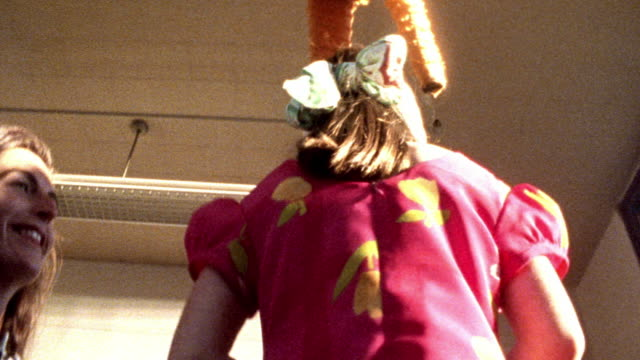 HIGH CONTRAST low angle MS blindfolded girl being spun for pinata game / pinata above her head in background