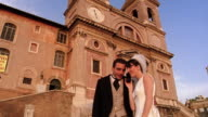 low angle bride + groom talking on cell phone in front of Trinita dei Monti / Rome, Italy