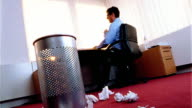 CANTED low angle businessman at desk throws crumpled paper onto floor littered with papers by trashcan in foreground