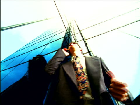 OVEREXPOSED low angle businessman talking on cellular phone + gesturing in victory by mirrored building