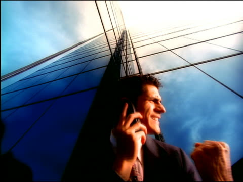 low angle businessman talking on cellular phone + raising arm in victory in front of mirrored building