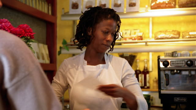 Low angle close up Black woman serving croissant to customer in cafe / taking money