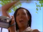 low angle close up Black woman with braids taking photo + shouting outdoors