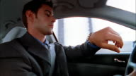 Low angle close up businessman checking watch while driving car