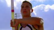 low angle close up Hispanic male pole vaulter lifting pole + starting to run