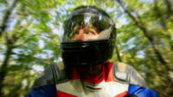 Low angle close up man wearing motorcycle helmet riding motorbike through woods / Brentwood, Essex, England