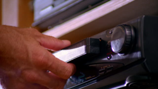 low angle close up man's hand pushing eject button + taking video tape out of VCR