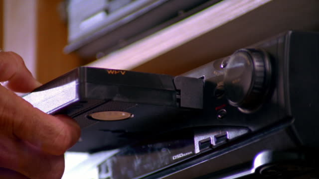 low angle close up man's hand putting video tape into VCR + pressing play