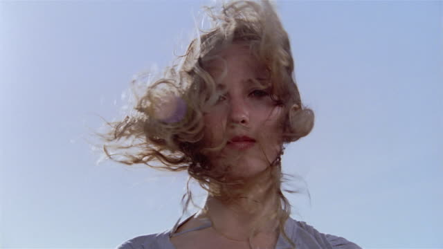 Low angle close up portrait of woman with hair blowing in wind