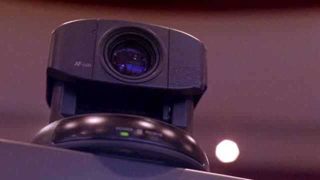 low angle close up teleconferencing camera rotating + tilting down + up