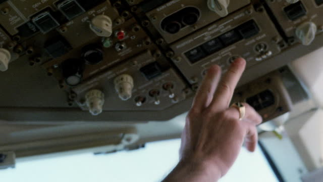 Low angle close up tilt down hands of pilot pushing switches in cockpit of airplane