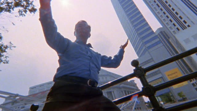 Low angle close up tracking shot mature Asian man doing Tai Chi / skyscrapers in background