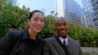 Low angle close up young Asian businesswoman and young Black businessman posing outdoors
