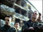 low angle MS dolly shot around group of men in military fatigues / ruins in background / Sarajevo, Bosnia-Herzegovina