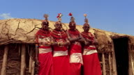 low angle MS dolly shot four young Masai tribeswomen standing in front of hut / Kenya