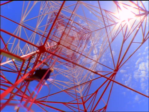 low angle dolly shot man climbing ladder of red + white radio tower