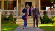 low angle dolly shot man in suit + children with backpacks leaving house with woman on porch watching