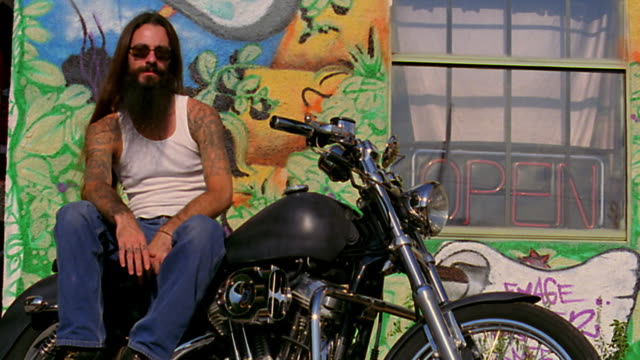 low angle dolly shot PORTRAIT man with long hair, sunglasses, + tattoos sitting on motorcycle / tattoo parlor in background