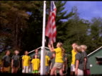 low angle dolly shot tilt up around group of children standing by flagpole as girl raises American flag at summer camp
