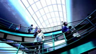 BLUE low angle dolly shot two indoor elevated walkways with man talking on cell phone + businesspeople walking across