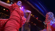 low angle dolly shot zoom in zoom out man singing on stage with women in red costumes dancing around him