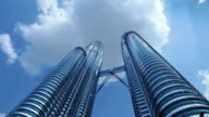 Low angle fast motion wide shot Petronas Twin Towers with clouds moving above/ Kuala Lumpur