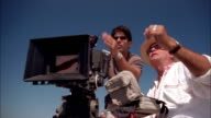 Low angle film director gesturing and talking beside cameraman on film location / Rio de Janeiro