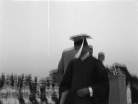 B/W 1965 low angle PAN graduate walks to podium, accepts diploma + shakes hands with man + returns to group
