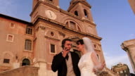 low angle groom giving cell phone to bride in front of Trinita dei Monti / Rome, Italy
