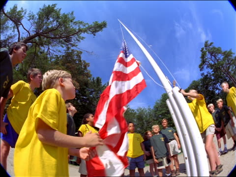 FISHEYE low angle group of children looking up as girl raises American flag at summer camp