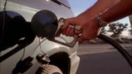 Low angle hands opening gas tank cover and placing gas pump nozzle in tank / pumping gas + removing nozzle