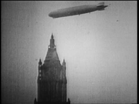 B/W 1929 low angle long shot Graf Zeppelin flying over Woolworth Building in NYC