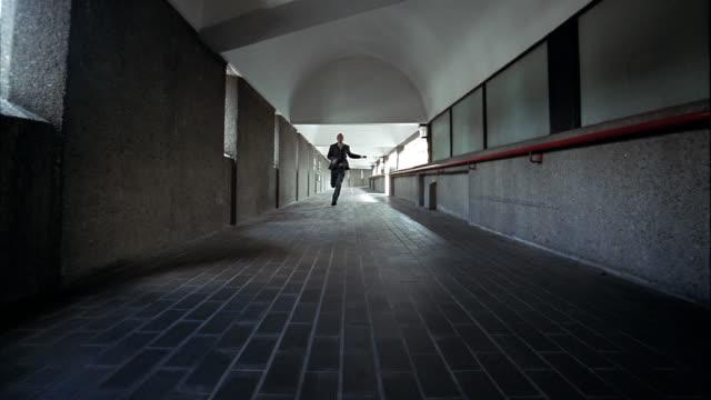 Low angle long shot man running down corridor towards CAM / pan man turning corner and running away from CAM