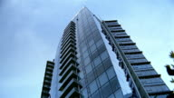 Low angle long shot modern glass and steel residential building in Vancouver / British Columbia, Canada