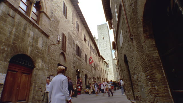 Low angle long shot people walking on San Gimignano street with medieval tower in background / Tuscany, Italy