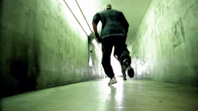 Low angle long shot three freerunners running down hallway away from CAM / jumping off walls
