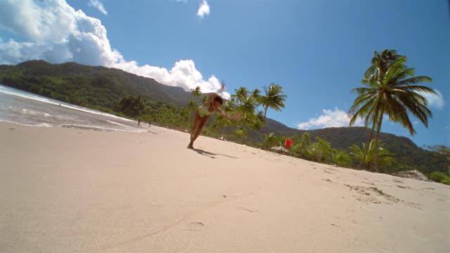 Low angle long shot woman running on beach and doing cartwheel / medium shot crouching down + smiling at CAM