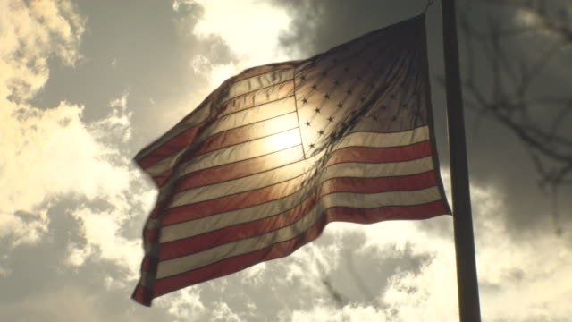 low angle looking up American flag flying high with the suns rays breaking through the clouds in the background sun shining through the flag