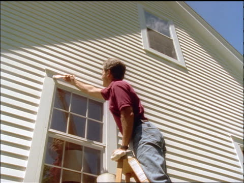 low angle man on ladder painting window trim on A-frame house