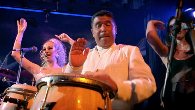 low angle MS man playing conga drums with two female backup singers dancing on stage