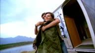 Low angle man putting blanket around woman in bikini / couple hugging outdoors beside trailer