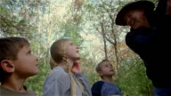Low angle man showing kids bark on tree on a hike