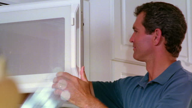 low angle PAN man taking container of food out of microwave