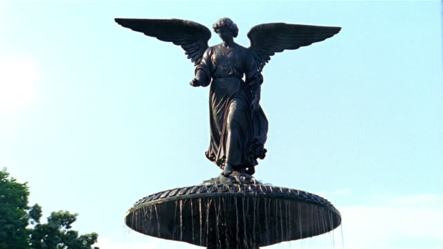 Low angle medium shot 'Angel of the Waters' statue on top of Bethesda Fountain in Central Park / New York City