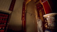 Low angle medium shot Asian woman walking down hall with Chinese signs, prayer candles burning