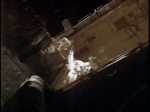 2005 low angle medium shot astronaut working on the International Space Station during space walk / STS114