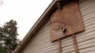 Low angle medium shot basketball being shot at hoop over garage